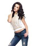 与长的头发的时装模特儿在蓝色牛仔裤穿戴了 免版税库存图片