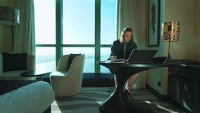 与长的头发的年轻商人研究膝上型计算机,键入文本,在办公室或旅馆客房认为 院长,上司工作 股票视频