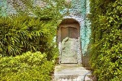 与长满的古色古香的石房子的生锈的铰链的老门 库存图片
