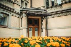 与门廊的老葡萄酒门在黄色花之间 旅行phot 免版税库存图片