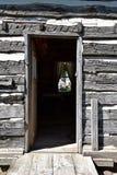 与门户开放主义的老原木小屋 图库摄影
