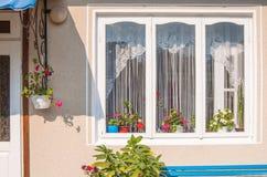 与门廊和花的舒适窗口在房子里 免版税图库摄影