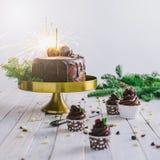 与闪烁发光物和杯形蛋糕莓果的黑暗的巧克力蛋糕在白色木背景 免版税库存照片