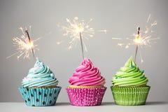 与闪烁发光物的三块杯形蛋糕 免版税库存照片