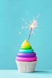 与闪烁发光物的五颜六色的杯形蛋糕 免版税图库摄影