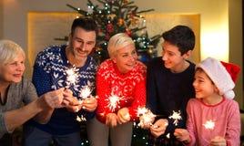与闪烁发光物的家庭在圣诞节时间 免版税库存照片