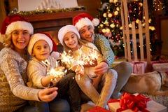 与闪烁发光物的家庭庆祝圣诞节的 库存图片