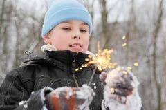 与闪烁发光物的小男孩作用在森林里 库存图片