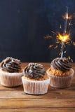与闪烁发光物的巧克力杯形蛋糕点燃在木背景 库存照片