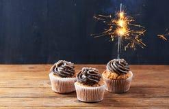与闪烁发光物的巧克力杯形蛋糕点燃在木背景 免版税库存图片