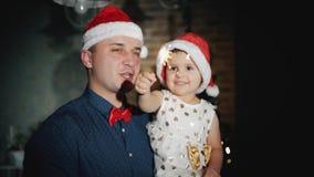 与闪烁发光物的快乐的家庭和戴在他们的头的圣诞老人项目帽子对圣诞树的脚微笑着 影视素材