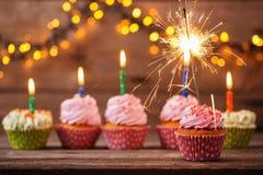 与闪烁发光物的杯形蛋糕在老木背景 免版税库存图片