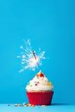 与闪烁发光物的杯形蛋糕在蓝色 免版税库存照片