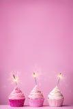 与闪烁发光物的桃红色杯形蛋糕 免版税库存图片