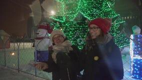 与闪烁发光物的母亲和女儿跳舞在圣诞树附近的降雪下在街道 影视素材