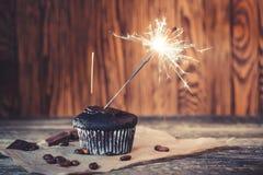与闪烁发光物的鲜美巧克力杯形蛋糕 在木背景的生日杯形蛋糕 党的可口杯形蛋糕 生日贺卡,拷贝温泉 免版税库存照片