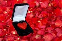 与闪烁心脏的干玫瑰花瓣背景在箱子 免版税图库摄影