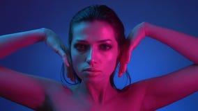 与闪烁构成的模型在与时兴她的手普遍姿势的蓝色和桃红色霓虹灯到照相机里 股票视频