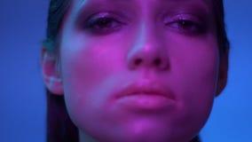 与闪烁构成的美妙的时装模特儿在反抗地观看入照相机的紫色霓虹灯在演播室 影视素材