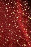 与闪烁的金黄星的红色缎布 免版税库存图片