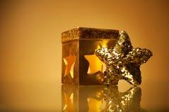 与闪耀的圣诞节星和蜡烛台的金黄魅力题材 免版税库存照片