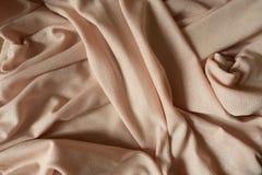 与闪耀的纤维的被折叠的米黄聚酯纺织品 库存照片
