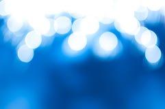 与闪闪发光和bokeh的不可思议的蓝色抽象背景 库存图片