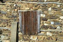 与闭合的快门的老传统窗口在一个被破坏的鹅卵石房子里 免版税库存照片