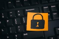 与闭合的挂锁的黄色纸笔记在一个黑键盘 库存照片