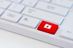 与闭合的挂锁象标志的红色钥匙在膝上型计算机键盘的一个文件夹 数据保护的概念 库存图片
