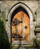 与闭合的木门的被成拱形的石门道入口 库存照片