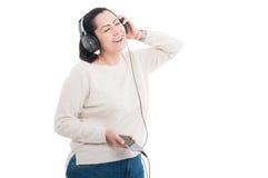 与闭合的眼睛的微笑的女孩听的音乐 免版税库存照片