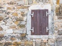 与闭合的窗口的窗口在粗砺的岩石墙壁关闭  免版税库存图片