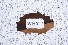 与问号和词为什么的白皮书笔记在木桌上的中心 库存照片