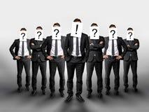 与问号在他们的头和一个商人的集团在中心有惊叹号 库存照片