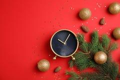 与闹钟、冷杉分支和装饰的平的位置构成在颜色背景 christmas countdown 免版税库存图片