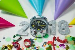 与闹钟、装饰和党帽子的新年2018年 免版税库存图片