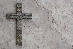 与阁下` s祷告的黑木十字架在灰色混凝土有镇压背景 免版税库存照片