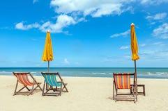 与阳伞的三张海滩睡椅在与克洛的美丽的海滩 免版税图库摄影