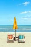 与阳伞的两张海滩睡椅在美丽的海滩 库存照片