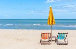 与阳伞的两张海滩睡椅在美丽的海滩 免版税库存图片