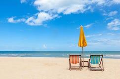 与阳伞的五颜六色的两张海滩睡椅在美丽的海滩w 免版税图库摄影