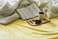 与阳光照亮的圣经的早晨咖啡 咖啡与基督徒圣经的 空白卧室 巧克力和咖啡杯 免版税库存照片