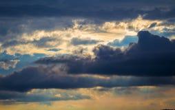 与阳光的风雨如磐的天空 与多雨云彩的日落场面 免版税库存照片