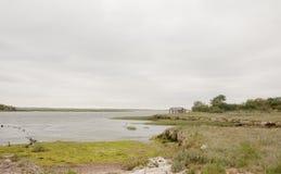 与阴暗天空净空的沿海场面和海湾登陆的岩石 免版税图库摄影