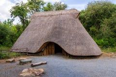 与阵营火,童年年龄人的解决的概念的老茅草屋顶村庄 库存图片