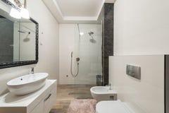 与阵雨客舱的现代卫生间内部在豪华别墅 免版税库存图片