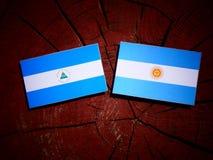 与阿根廷旗子的尼加拉瓜的旗子在被隔绝的树桩 向量例证