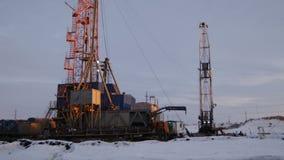 与附录的大橙色钢抽油装置在雪风景中 股票录像
