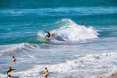 与附近孩子的冲浪者佩带的保温潜水服骑马小波浪在海洋 图库摄影